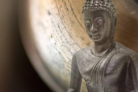 Bust of buddha figurine from black stone with macro bell photo for background