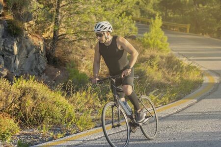 male biker cycling on a mountain road - Sport and active life concept