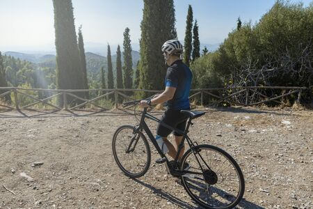 Male cyclist walking with his bike before or after training