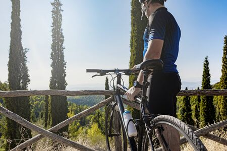 Male cyclist standing with his bike before or after training watching the view Imagens