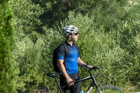 Male cyclist standing with his bike before or after training