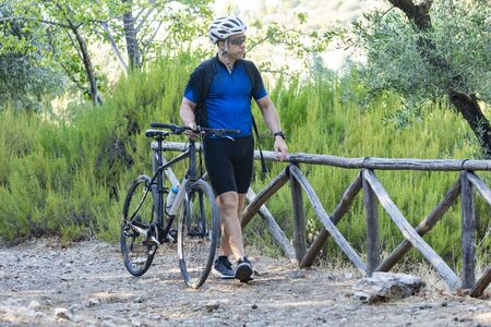 male athletic cyclist walking with his bike on a mountain path