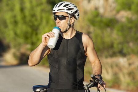 male cyclist resting and drinking isotonic drink after training with his bike