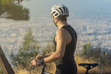 Male cyclist standing with his bike watching the view before or after training