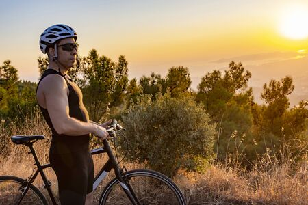 Male biker watching the sunset while resting after ride - training 版權商用圖片
