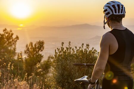 Male biker watching the sunset while resting after ride - training Imagens