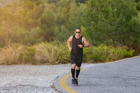 male athlete runner while running in the mountain road 版權商用圖片