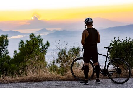 Male biker watching the sunset while resting after ride - training Stockfoto
