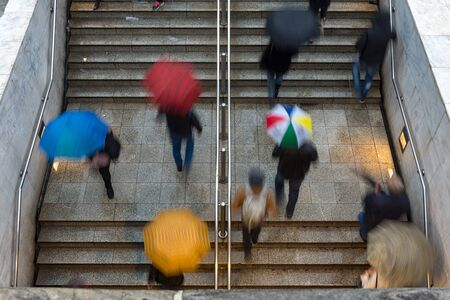 overhead view of people walking towards and away from the entrance to the underground train station under rain with umbrellas - bad weather