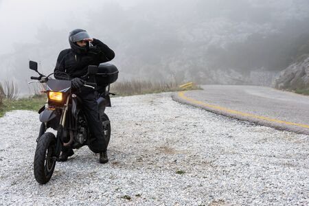 Rider trying to see through the fog on an adventure ride on the mountains with his motorbike - adventure ride project 版權商用圖片