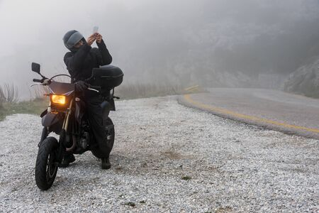 Rider is trying to find signal on his mobile on a foggy day ride on the mountains with his motorbike - adventure ride project 版權商用圖片