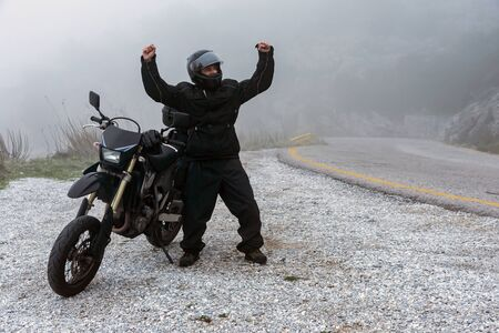 Rider celebrate his successful ride on a foggy day in the mountains with his motorbike - adventure with motorcycle project