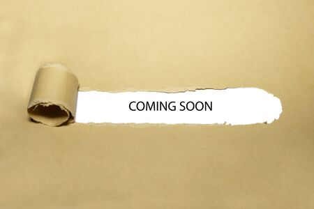 The phrase Coming Soon appearing behind ripped brown paper. Concept about upcoming promising event approaching in near future.