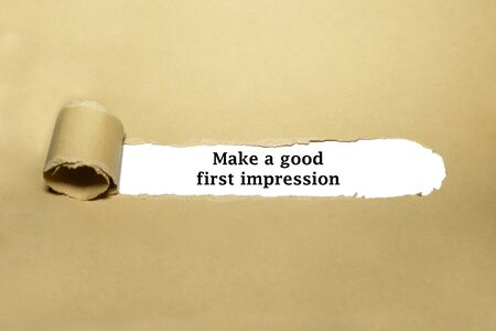 Motivational advice Make A Good First Impression appearing behind ripped brown paper. 版權商用圖片