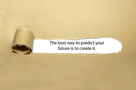 Cita inspiradora La mejor manera de predecir su futuro es crearlo. apareciendo detrás de papel marrón rasgado. Foto de archivo