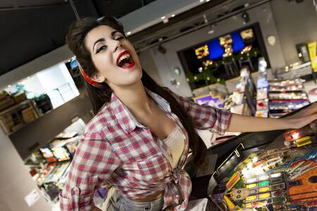 young pin up girl plays pinball in athens pinball museum Zdjęcie Seryjne