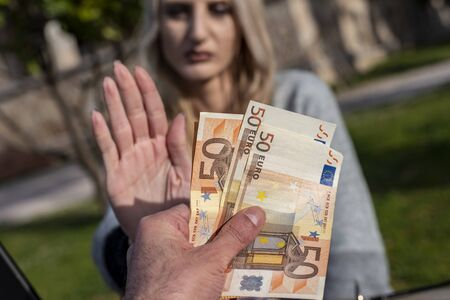 Blond female woman refuses to accept money - concept of anti corruption and bribery