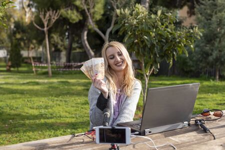 Female blond blogger demonstrates the money earned from internet services - working outdoors -  cash for review products and services - youtubers and influencers work concept