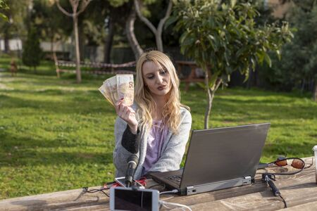 Female blond blogger demonstrates the money earned from internet services - working outdoors -  cash for review products and services - and influencers work concept Zdjęcie Seryjne