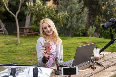Female blond blogger interacting  her mobile - working outdoors - traveling the  -  and influencers work concept Zdjęcie Seryjne