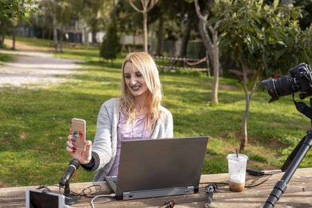 Female blond blogger interacting  her mobile - working outdoors - traveling the  influencers work concept Zdjęcie Seryjne
