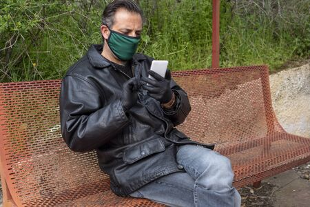 Man wearing mask and gloves sitting on a bench during covid 19 pandemic threat and looking his smartphone