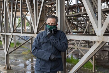 Man wearing mask and gloves during covid 19 pandemic standing and looking worried