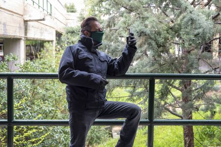 Man wearing mask and gloves during covid 19 pandemic threat and looking his smartphone