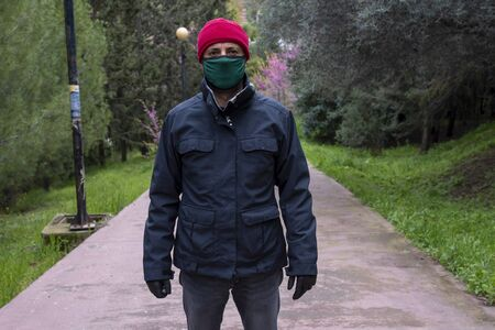 Man with red hat wearing mask and gloves during covid 19 pandemic threat