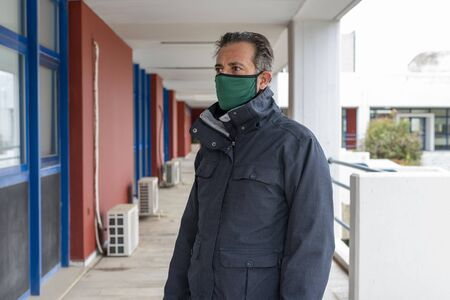 Man wearing mask and gloves during covid 19 pandemic threat standing outside from an closed building - virus protection project