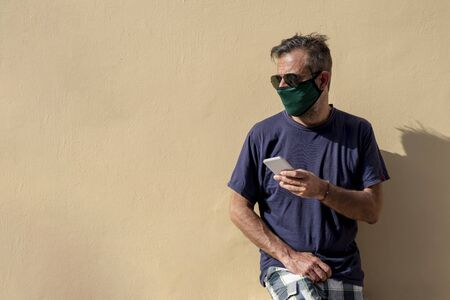 handsome mature man with surgical medical mask holding cellphone, 