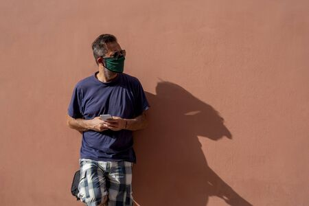 mature man with surgical medical mask holding cellphone, 