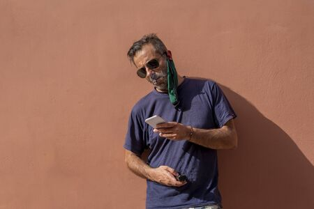handsome mature man, tired of the heat, has taken off his protective mask and he is smoking a cigarette ... he holds and looks at his cell phone - covid 19 project Imagens