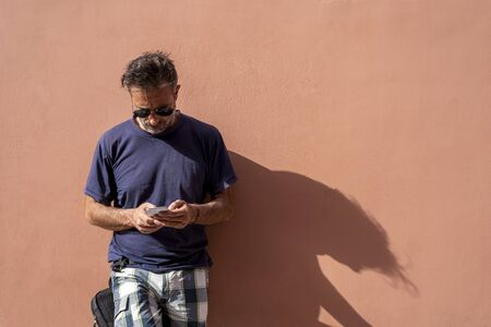 handsome Man Posing Isolated Over empty Wall Background Using his Mobile Phone on a sunny day wearing sunglasses
