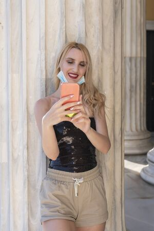 beautifil blond girl smiling with face mask after lockdown reopening - She is enjoying her walk having fun, chating with friends, taking selfies outside marble building - socializing again project 版權商用圖片