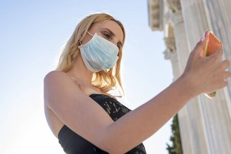 Young blond woman with face mask using tracking app on mobile smart phone - New normal everyday lifestyle concept with milenials sharing content at social media platforms Imagens