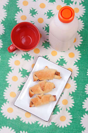 Plastic bottle with clabber, cup and bagels on tablecloth  photo