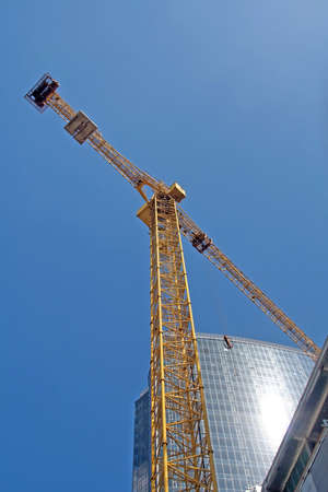Crane and modern building in the blue sky photo