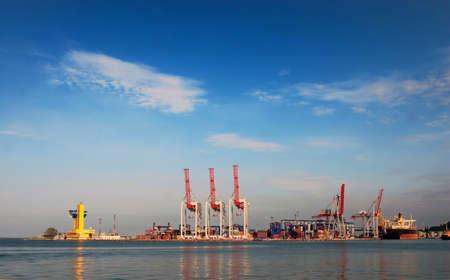 Sea port at sunrise, cranes and ships
