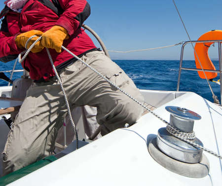 sailing yacht: Man holding rope on sailing boat Stock Photo