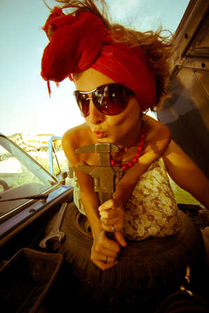Vintage girl with tool repairing car Stock Photo