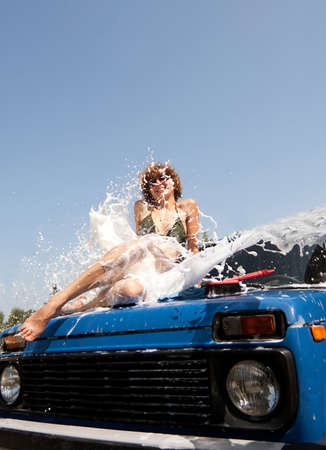 Girl in foam splash sitting on car