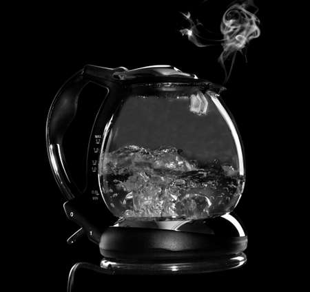 Kettle with boiling water and steam isolated with clipping path on black background photo