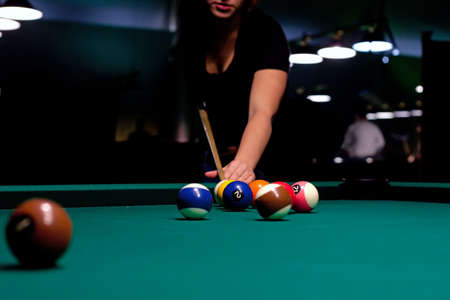 Woman trying to hit the ball in billiard photo