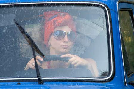 Vintage girl driving car under rain
