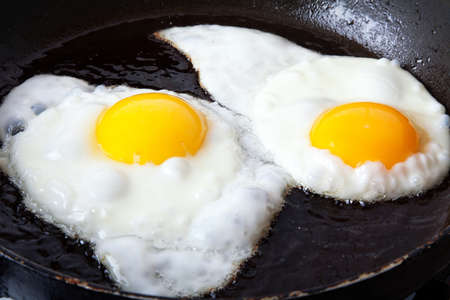 Two eggs frying in oil