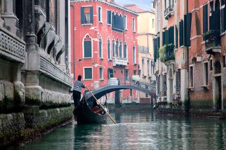 Gondoliero sailing in Venice narrow channel Stockfoto