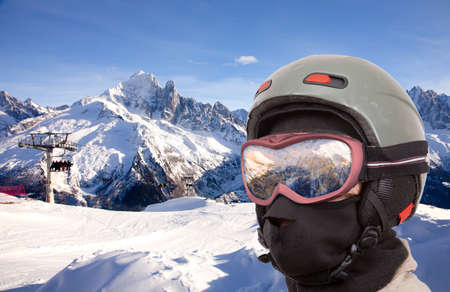 Collage with alpine slope and closeup skier in helmet
