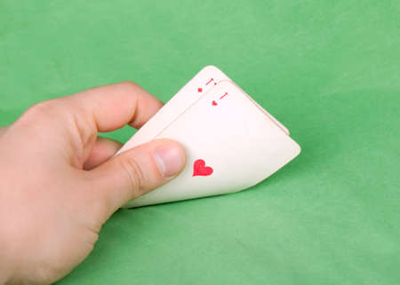 Gamblers hand with two aces on green table  photo