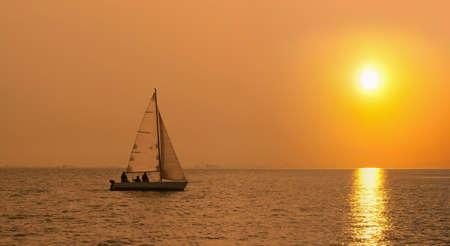 Bateau à voile dans la mer au coucher du soleil Banque d'images